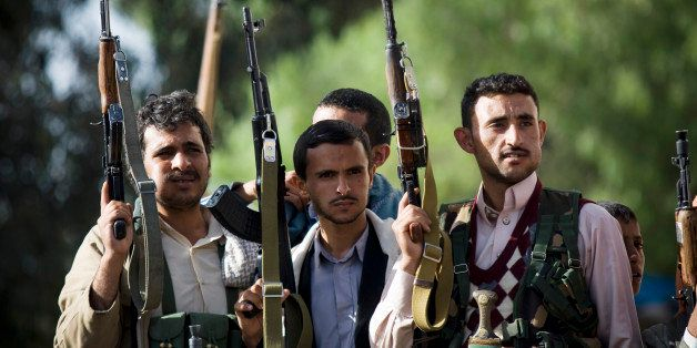 In this Thursday, April 16, 2015 photo, Shiite rebels, known as Houthis, hold up their weapons as they...