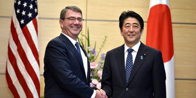 U.S. Defense Secretary Ash Carter, left, shakes hands with Japan's Prime Minister Shinzo Abe at the start of their meeting at