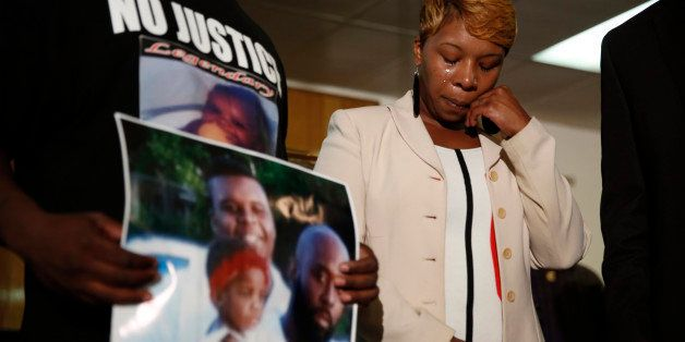 FILE - In this Aug. 11, 2014 file photo, Lesley McSpadden, the mother of 18-year-old Michael Brown, wipes away tears as Brown