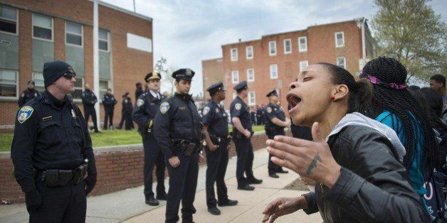 Demonstrators yell at police as they protest the death Freddie Gray, an African American man who died of spinal cord injuries