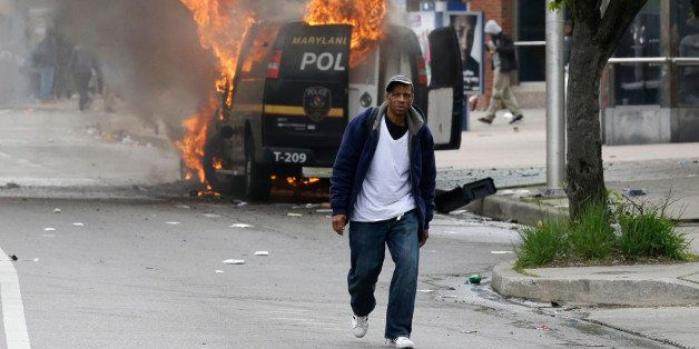 A man walks past a burning police vehicle, Monday, April 27, 2015, during unrest following the funeral of Freddie Gray in Bal