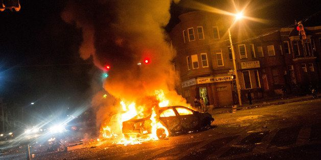 BALTIMORE, MD - APRIL 27:  Two cars burn in the middle of an intersection at New Shiloh Baptist Church on April 27, 2015 in B