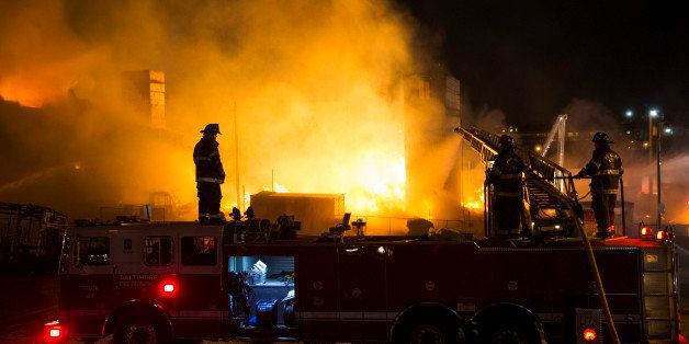 Firefighters battle a blaze, Monday, April 27, 2015, after rioters plunged part of Baltimore into chaos, torching a pharmacy,