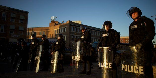 BALTIMORE, MD - APRIL 28:  Riot police are illuminated by late afternoon light as they line the street to form a blockade aft
