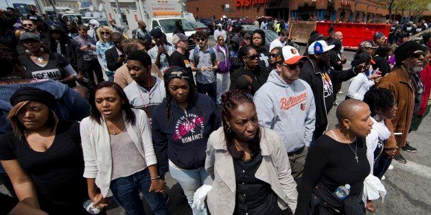"People clasp hand and sing the hymn ""Amazing Grace"" Tuesday, April 28, 2015, in Baltimore, in the aftermath of rioting follow"