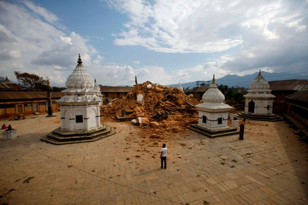 People look at the debris of one of the oldest temples after it was damaged in Saturday's earthquake, in Kathmandu, Nepal,