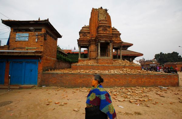 A Nepalese woman walks past a collapsed temple in Bhaktapur Durbar Square after an earthquake in Kathmandu, Nepal, Sunday, Ap