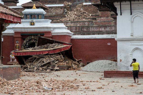 KATHMANDU, NEPAL - APRIL 25: A young man speaks on the phone in front of a collapsed temple in the city center following an e