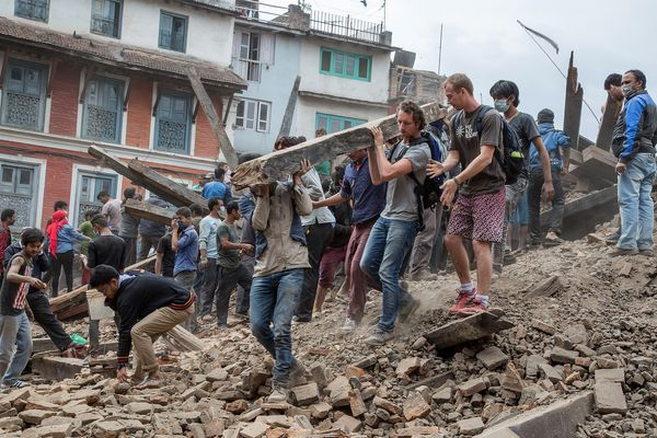 KATHMANDU, NEPAL - APRIL 25: Emergency workers and bystanders clear debris while searching for survivors under a collapsed te