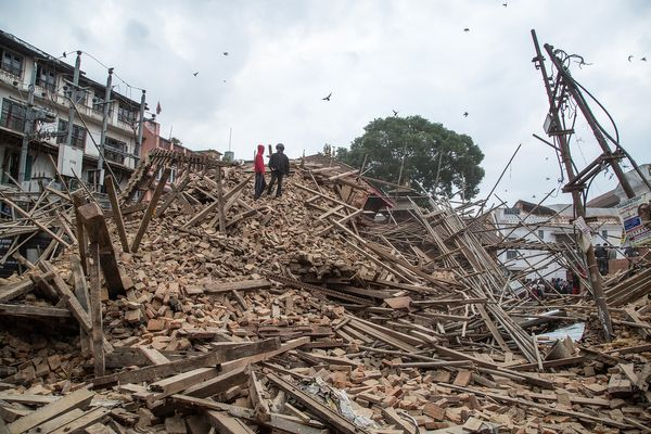 KATHMANDU, NEPAL - APRIL 25: People stand on top of debris from a collapsed building at Basantapur Durbar Square watching the