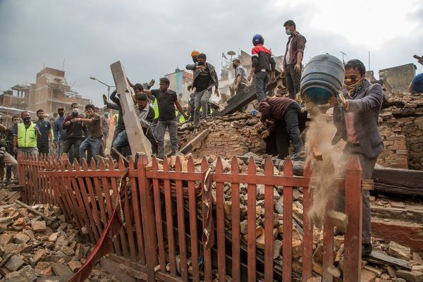 KATHMANDU, NEPAL - APRIL 25: Bystanders watch as emergency teams clear debris in Basantapur Durbar Square following an earthq