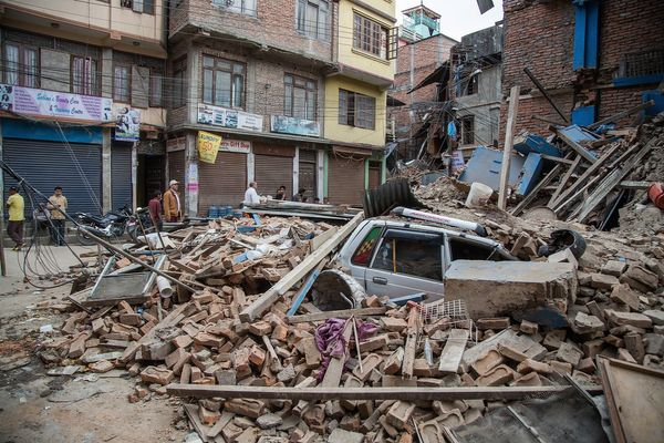 KATHMANDU, NEPAL - APRIL 25: A taxi is buried under debris from a collapsed building in Thamel following an earthquake on Apr