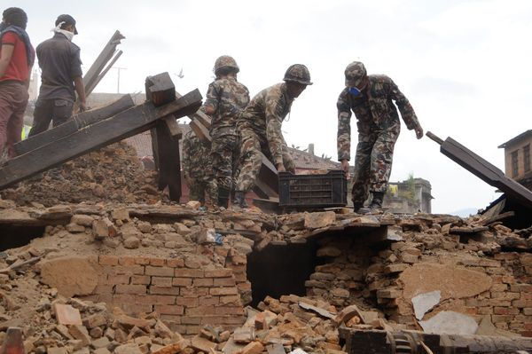 KATHMANDU, NEPAL - APRIL 25 : Soldiers help with rescue work at the site of a building that collapsed after an earthquake in