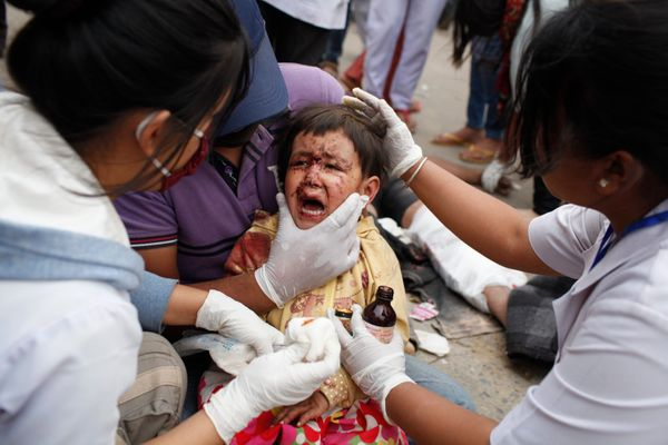 KATHMANDU, NEPAL - APRIL 25: (EDITORS NOTE: Image is highest resolution available.) A child receives treatment outside the em