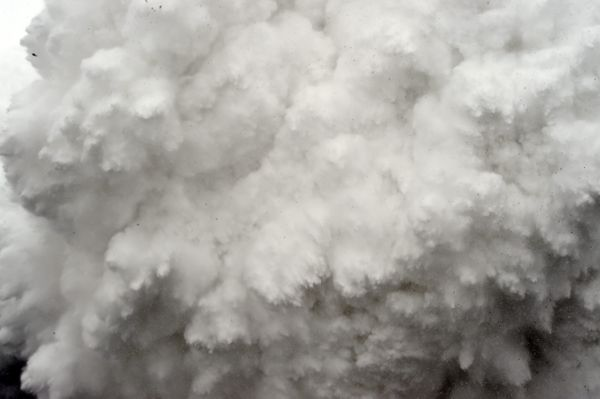 In this photograph taken on April 25, 2015, a cloud of snow and debris triggered by an earthquake flies towards Everest Base