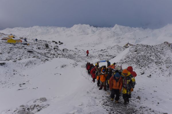 An injured person is carried by rescue members to be airlifted by rescue helicopter at Everest Base Camp on April 26, 2015, a