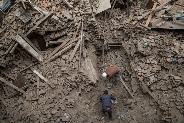 BHAKTAPUR, NEPAL - APRIL 26:  Two men help clear debris after buildings collapsed on April 26, 2015 in Bhaktapur, Nepal. A ma