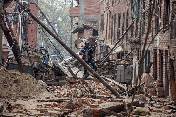 BHAKTAPUR, NEPAL - APRIL 26:  A man runs down a street covered in debris after buildings collapsed on April 26, 2015 in Bhakt