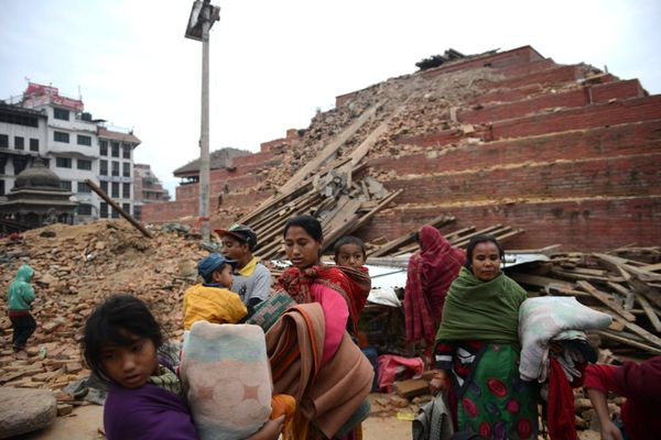 Nepalese residents walk beside buildings severely damaged by an earthquake on Kathmandu on April 26, 2015. Rescuers in Nepal