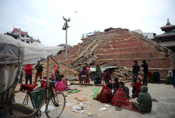 Nepalese residents walk past buildings severely damaged by an earthquake on Kathmandu on April 26, 2015. Rescuers in Nepal se