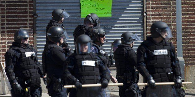 Policemen take a position outside a store at the Western District in Baltimore, Maryland on April 29, 2015. Riot police in th