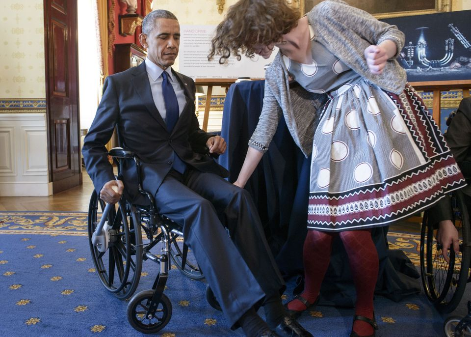 President Barack Obama tries a wheel chair powered by a rowing motion designed by Kaitlin Reed of Massachusetts during the 20