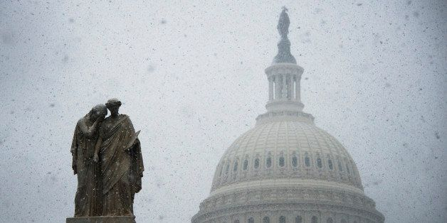 Snow begins to gather on a statue outside the US Capitol Building in Washington, DC, December 10, 2013.  Fresh winter snow mo