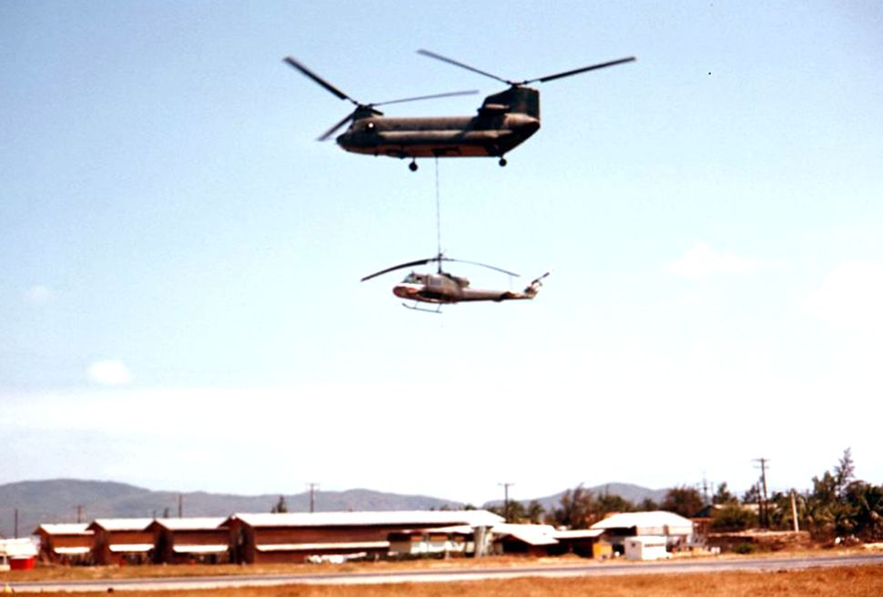 A Chinook helicopter rescuing a damaged one.