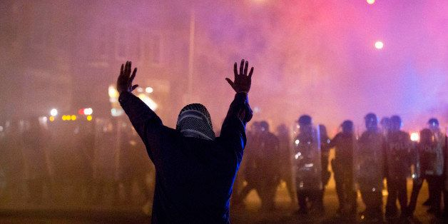 A protestor faces police enforcing a curfew Tuesday, April 28, 2015, in Baltimore. A line of police behind riot shields hurle