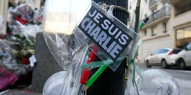 Flowers are laid near the headquarters of magazine Charlie Hebdo in Paris, Friday Feb. 6, 2015. Brothers Said and Cherif Koua