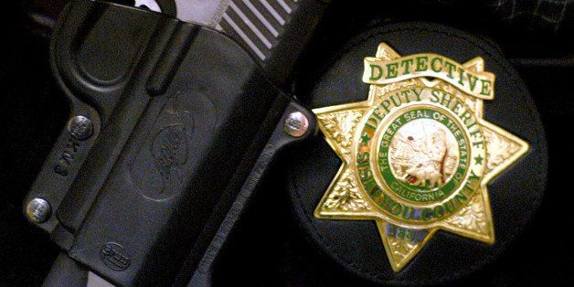 Siskiyou County Sheriff Detective Darrel Lemos, 33, wears his badge, shown Wednesday, Feb. 26, 3003, in Yreka, Calif., on his