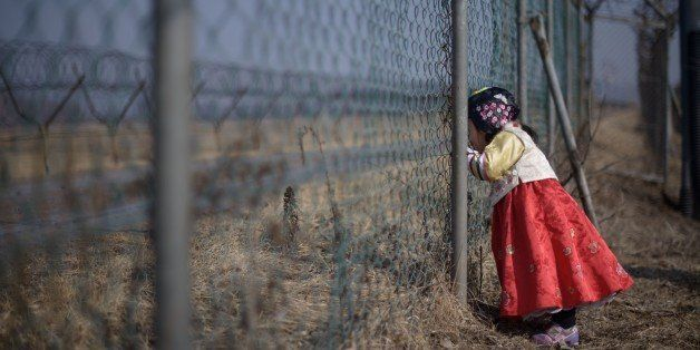 A girl wearing a traditional hanbok dress stands at a military fence facing towards North Korea at Imjingak park, south of th