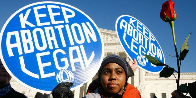 WASHINGTON - JANUARY 22:  Local pro-choice activist Lisa King holds a sign in front of the U.S. Supreme Court as a pro-life a