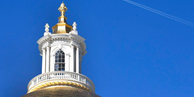 An airplane leaves a trail as it flies the blue sky above the Statehouse in Boston, Thursday, Feb. 20, 2014. (AP Photo/Elise