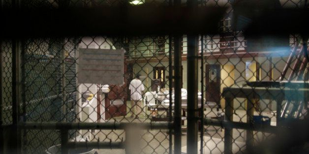 In this photo reviewed by a U.S. Department of Defense official, a prisoner walks through a communal pod inside an area of th