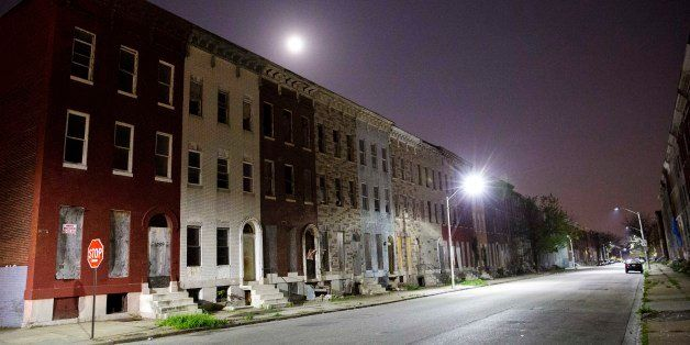 The moon rises above a block of blighted row houses in the neighborhood where Freddie Gray was arrested as a six day curfew w