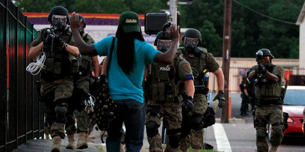 FILE - In this Aug. 11, 2014, file photo, police wearing riot gear walk toward a man with his hands raised in Ferguson, Mo. T