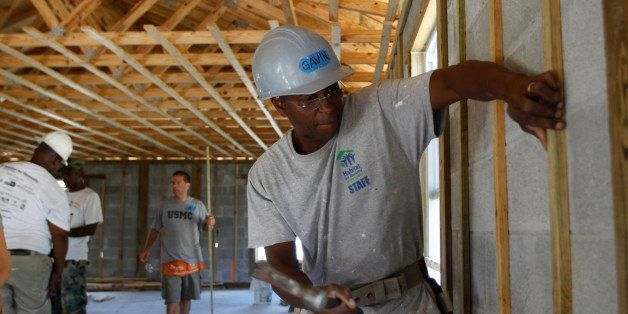 Gavin Canady, of Habitat for Humanity, right, works with former U.S. Marine Dan Caporale, of Fort Lauderdale, Fla., center, i