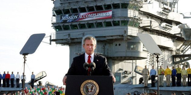 """FILE - In this May 1, 2003 file photo, President George W. Bush speaks aboard the aircraft carrier USS Abraham Lincoln off the California coast. As slogans go, President Barack Obama's promise of the """"light of a new day"""" in Afghanistan isn't as catchy as the """"Mission Accomplished"""" banner that hung across the USS Abraham Lincoln the day President George W. Bush announced the end of major combat operations in Iraq. (AP Photo/J. Scott Applewhite, File)"""