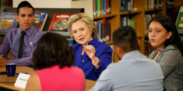 Democratic presidential candidate Hillary Rodham Clinton speaks with a group, including students, about immigration during a