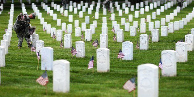 A soldier from the 3rd US Infantry Regiment, 'The Old Guard,' places flags at grave sites during the 'Flags-In' ceremony at A