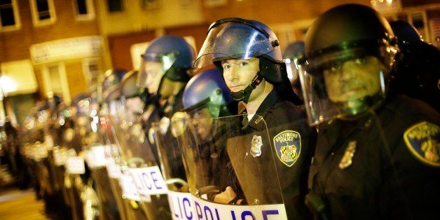 Police line up in riot gear after a 10 p.m. curfew went into effect Thursday, April 30, 2015, in Baltimore. The curfew was im