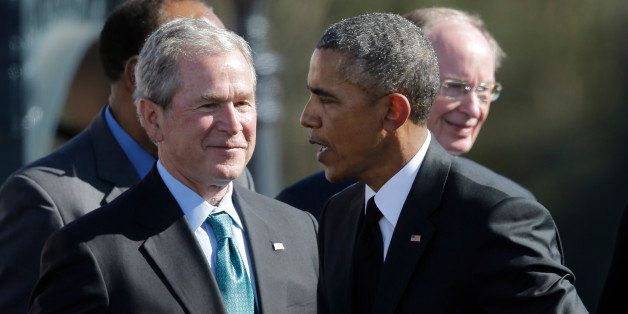 President Barack Obama shakes hands with Former President George W. Bush after Obama spoke to a large crowd near the Edmund P