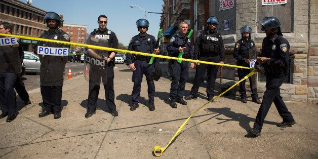 BALTIMORE, MD - MAY 4:  An officer rolls out police tape as other officers form a line to block North Ave., near the site of