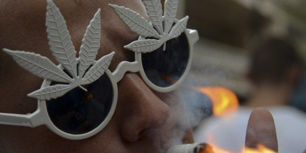 A man smokes marijuana during a demo for its legalization, in Medellin, Antioquia department, Colombia on May 2, 2015. The de