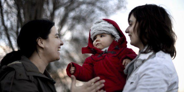 Same sex couple Olga Miranda (R) and Matilde Custodio (L) hold their daughter Carolina during a walk in the park in Lisbon on
