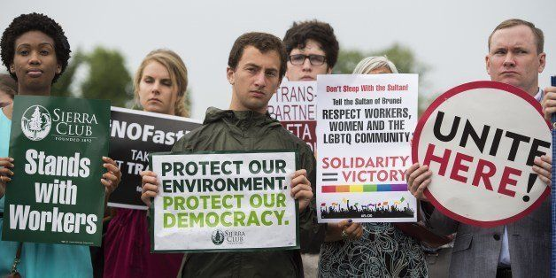Activists stand with placards opposing the Trans-Pacific Partnership (TPP) during a news conference on Capitol Hill in Washin