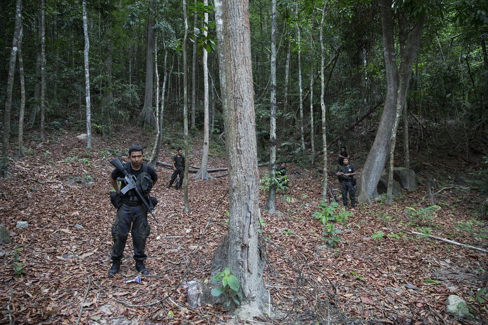 Policemen take position near the abandoned human trafficking camp in the jungle close the Thailand border at Bukit Wang Burma