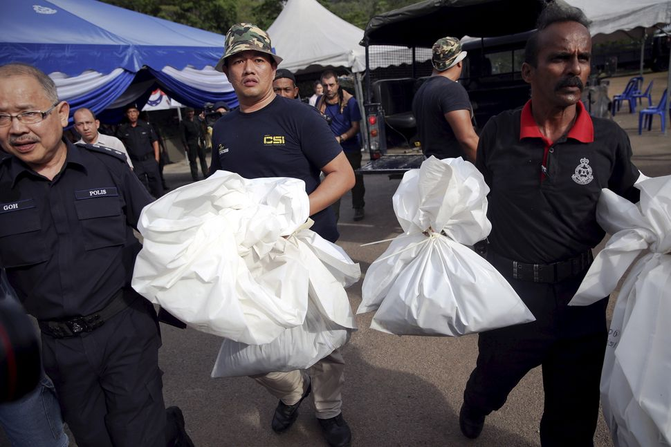 Forensic policemen carry body bags with human remains found at the site of human trafficking camps in the jungle close the Th