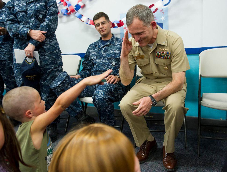 Capt. Michael W. Baze, commanding officer of the amphibious assault ship USS America (LHA 6), returns a salute from a student
